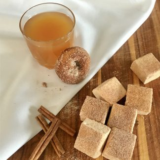 Apple Cider Donut Marshmallows shown with apple cider, an apple cider donut, and cinnamon sticks.