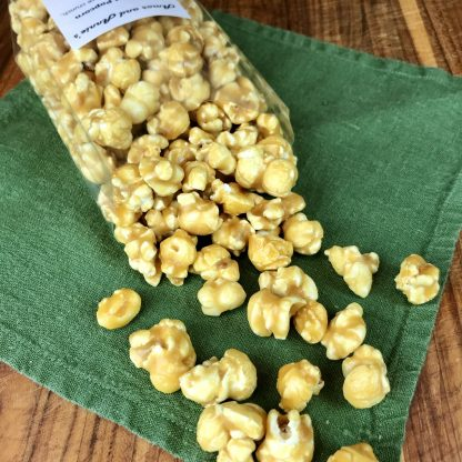 Caramel popcorn spilling out of a clear bag onto a green napkin which is on a wooden board
