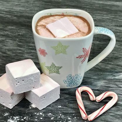 A cup of hot chocolate with a peppermint marshmallow melting in it and with other peppermint marshmallows and candy canes on a dark marble board