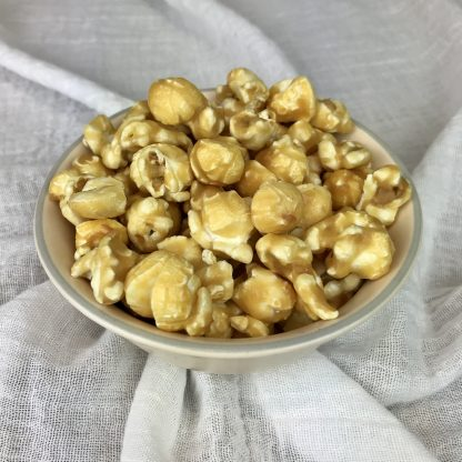 Caramel popcorn piled in a ceramic bowl setter on a white cloth