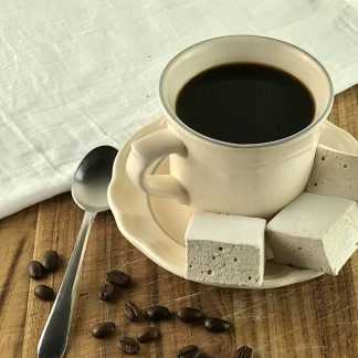 Three coffee marshmallows setting on a saucer with a cup of coffee. Coffee beans and a spoon are to the left of the saucer.