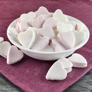 A white bowl of small white and pink heart-shaped marshmallows setting on a pink cloth.