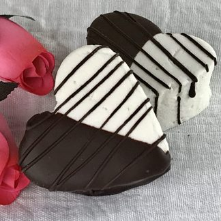 Two large marshmallow hearts half dipped in dark chocolate with additional drizzled chocolate setting on a white cloth with pink roses