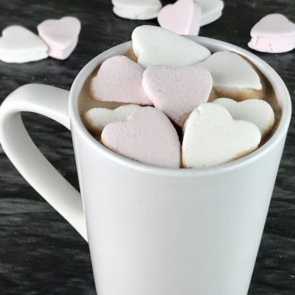 A white mug of hot cocoa topped with mini marshmallow hearts in pink and white setting on a dark marble board with a few extra heart mallows laying about.