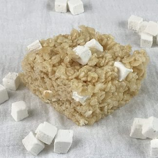 A crisp rice treat with homemade mini marshmallows on a white cloth with additional mini mallows sprinkled around