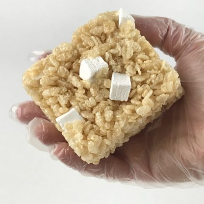 A gloved hand holding a crisp rice treat with homemade mini marshmallows with a white background