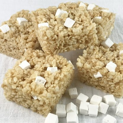 Five crisp rice treats with homemade mini marshmallows stacked on a white cloth with additional mini mallows sprinkled around