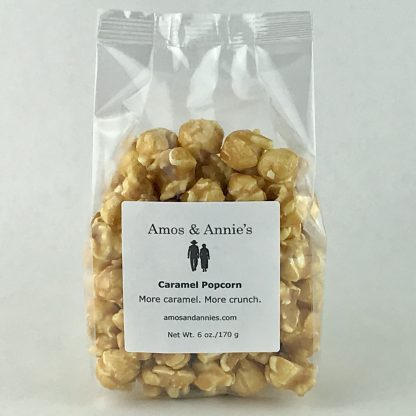 Caramel popcorn in a clear bag setting on a white background