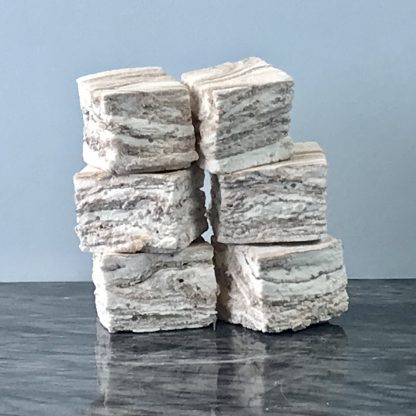 Two stacks each with three chocolate vanilla swirl marshmallows. They are setting on a dark marble board with a grey background.