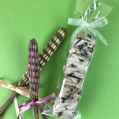A clear bag containing four marshmallows and tied with organza ribbon. Two lavender sachets set beside the bag. They are all setting on an apple green background.