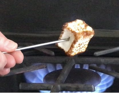 A vanilla marshmallow being toasted over a gas flame.