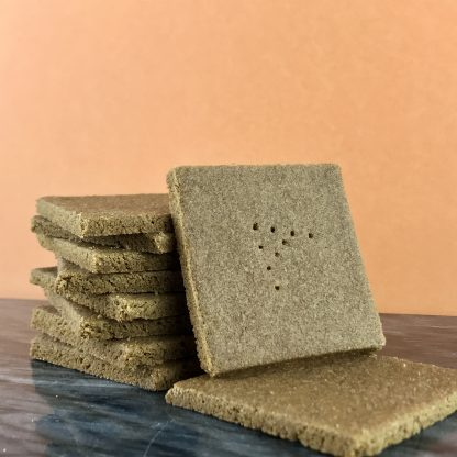 There is a stack of gluten-free graham crackers with one graham leaning against the stack. A capital 'A' is stamped on top of each graham. The crackers set on a dark marble board with a peach-colored background.