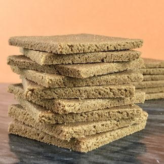 A stack of gluten-free graham crackers on a dark marble board. There is another stack of grahams in the background.