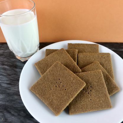 Seven gluten-free graham crackers are nestled onto a white plate, which is setting on a dark marble board. There is also a glass of milk and the background is peach-colored.