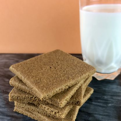 A stack of gluten-free graham crackers sets on a dark marble board. A capital 'A' is stamped onto the top of each cracker. There is a glass of milk and a peach-colored background.
