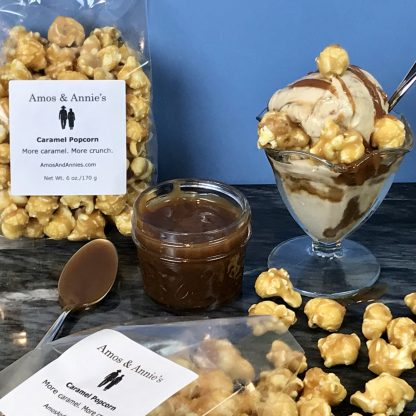 There is a dish of ice cream with caramel sauce drizzled on it and with a few pieces of caramel popcorn. There is also a small jar of caramel sauce with a spoon in it and an unopened bag of caramel popcorn. Lastly, there is an open bag of caramels popcorn with some spilled on the table.