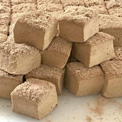 A pile of shoofly pie marshmallows sets on a white cutting board. The marshmallows are partially coated in crumbs.