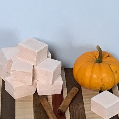 A pile of pumpkin spice marshmallows sets on a wooden board. A miniature pumpkin and two cinnamon sticks are also on the board. The background color is light blue.